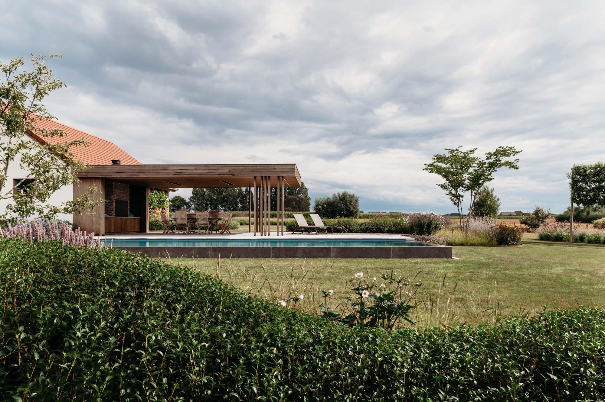 Moderne landschapstuin met modern poolhouse in padouk en biozwembad