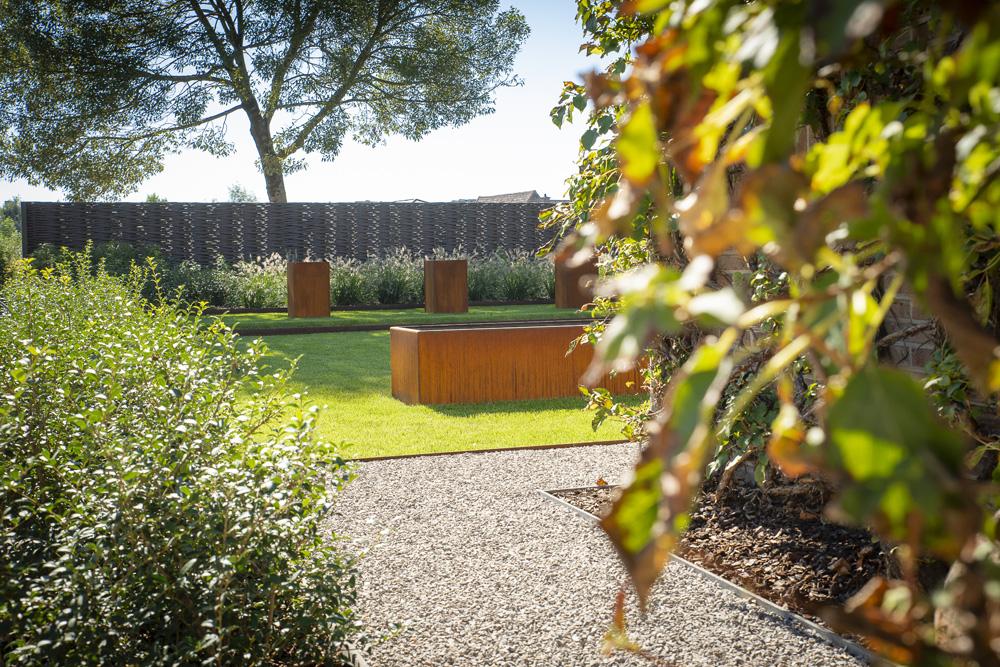 Hedendaagse tuin met cortenstaal en zitbank