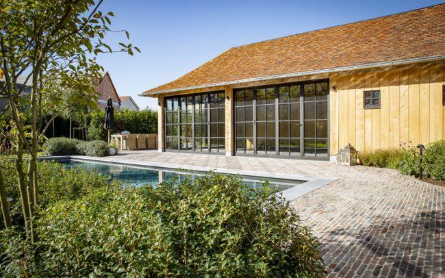 Landelijke binnentuin met eiken bijgebouw en biozwembad
